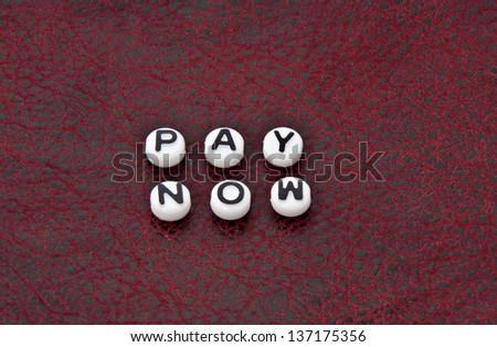 The words pay now, are in black and white alphabet beads, on a black and red textured leather background.