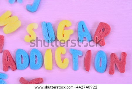 The words Sugar Addiction on pink table - stock photo