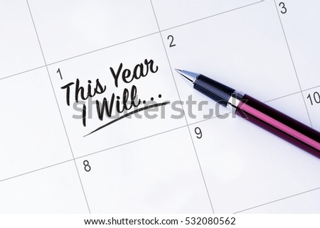 The words This Year I Will... written on a calendar planner to remind you an important appointment with a pen on isolated white background. New Year concepts of goal and objective.