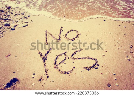 The words YES and NO written in sand  with a wave washing over it