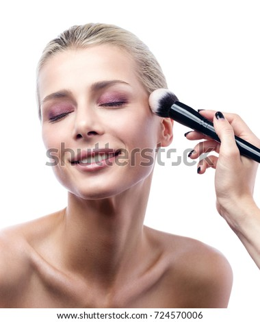 The work of a professional makeup artist. The beautiful young woman's face and brush the powder in close-up. Smile, eyes closed with pleasure. Beauty portrait isolated on white background