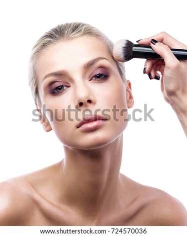 The work of a professional makeup artist. The beautiful young woman's face and brush the powder in close-up. Beauty portrait isolated on white background.