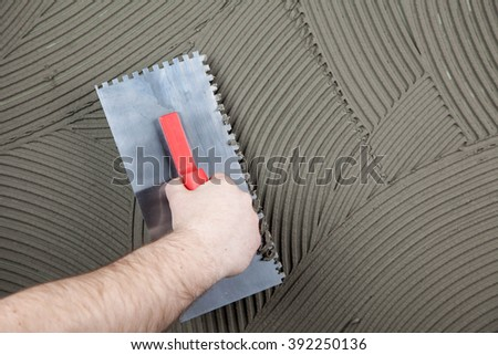 the worker applies glue for a tile on a wall  - stock photo