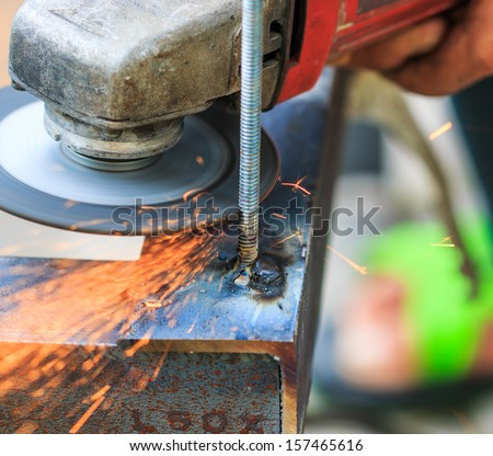 The worker cut steel and Worker cutting metal with grinder. Sparks while grinding iron