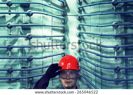 The worker in a helmet at factory.Industrial interior. - stock photo