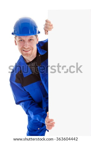 The worker in blue uniform and safety helmet holding blank sign billboard, isolated on white