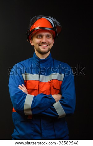 The worker in overalls and a helmet on a black background