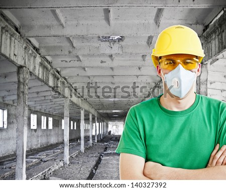 The worker in protective means. Headshot of a worker in protective workwear  inside against the support beams of the old empty room - stock photo