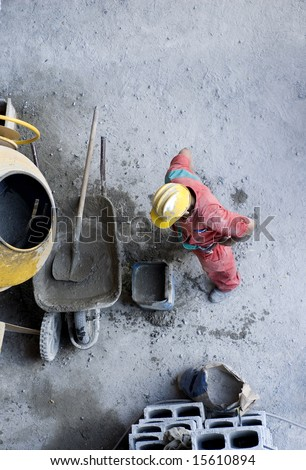 The worker is mixing concrete by cinder blocks in a wheel barrel.  Photo is taking from a vantage point above.  Vertically framed shot. - stock photo