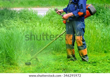 The worker of a garden cuts off a grass. The man in a uniform of the general worker works at a lawn. Work of municipal services on improvement of territories. - stock photo