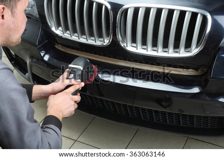 The worker polishes a bumper car cowl with the electric tool. Close up - stock photo