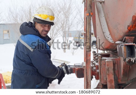 The worker prepares the drain device for pumping of fuel from a tanker - stock photo