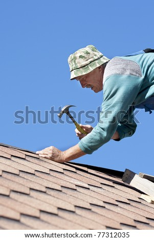 The worker repairs an apartment house roof