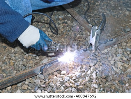 The worker spends electric welding work at the construction site - stock photo
