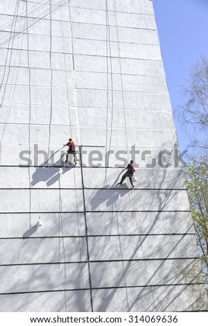 The workers  seals hermetically seams of the panel house. Work at height.