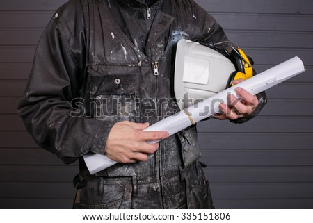 The workman holds in his hand a white protective helmet and construction drawings in Finland. The Worker's coverall is dirty. - stock photo