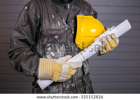 The workman holds in his hand a yellow protective helmet and construction drawings in Finland. The Worker's coverall is dirty.  - stock photo