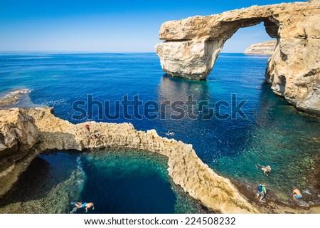 The world famous Azure Window in Gozo island - Mediterranean nature wonder in the beautiful Malta - Unrecognizable touristic scuba divers - stock photo