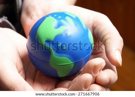The world of Earth is secured safely in the palms of human hands. - stock photo