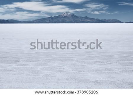 The world's largest salt flat and dormant volcano Tunupa at the far background,  Salar de Uyuni, Bolivia - stock photo
