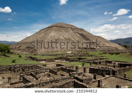 the world's third largest pyramid, the pyramid of the Sun in Teotihuacan with ruin walls in the foreground on a rare smog free day  - stock photo