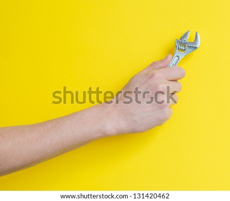The wrench in his hand on a yellow background - stock photo