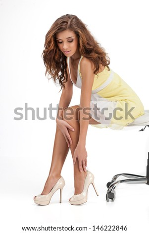 The wrong size. Beautiful young women sitting on the chair and touching her legs while isolated on white - stock photo