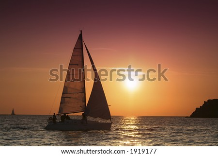 The yacht comes nearer to an island. The sails are filled by a wind. The day begins. - stock photo