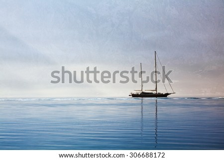 The yacht floats in the sea in the early morning on the background of the misty mountains - stock photo