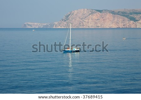 The yacht is moving across the sea with mountains on background - stock photo