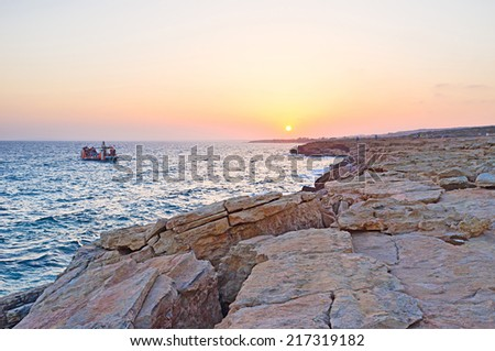 The yacht sails along the coastline of Famagusta bay and enjoy the sunset over Ayia Napa, Cyprus. - stock photo