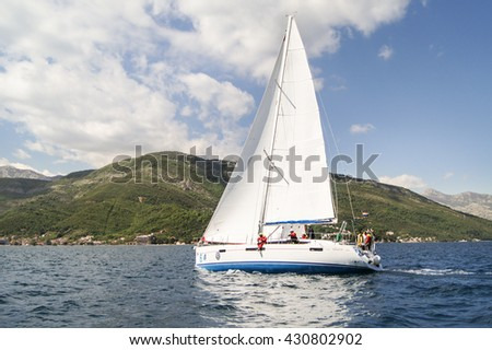 "The yacht with a crew. Tivat, Montenegro - 26 April, 2016. Regatta ""Russian stream"" in God-Katorskaya bay of the Adriatic Sea off the coast of Montenegro. - stock photo"