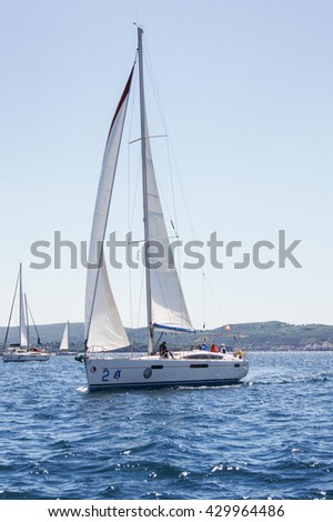 """The yacht with a sail. Tivat, Montenegro - 26 April, 2016. Regatta """"Russian stream"""" in God-Katorskaya bay of the Adriatic Sea off the coast of Montenegro. - stock photo"""