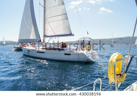 """The yacht with people running toward the shore. Tivat, Montenegro - 26 April, 2016. Regatta """"Russian stream"""" in God-Katorskaya bay of the Adriatic Sea off the coast of Montenegro. - stock photo"""