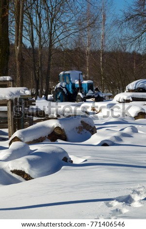 The yard and the tractor in the village were covered with snow
