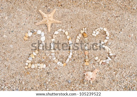 The year 2013 made of small stones on the sandy beach - stock photo