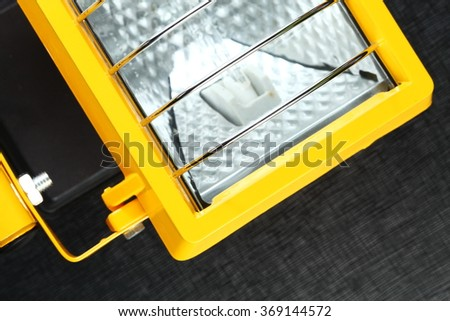 The yellow color spotlight unit with stainless steel protection guard represent the hardware and lighting equipment concept related idea.
