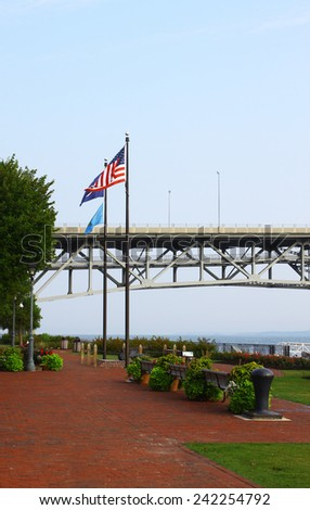 The Yorktown Riverwalk along the York river with the Coleman bridge in the background in Yorktown Virginia on a summer day with the American, County and State flags flying on a hazy, breezy summer day - stock photo