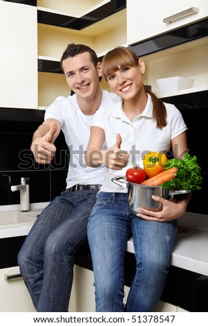 The young attractive couple sits at kitchen - stock photo