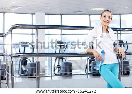 The young attractive girl with a water bottle in fitness club - stock photo