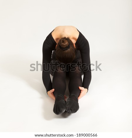 The young ballet dancer is sitting in front of the camera - stock photo