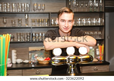 The young barman serving behind the bar (the pumping device). - stock photo