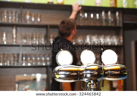 The young barman serving behind the bar (the pumping device).