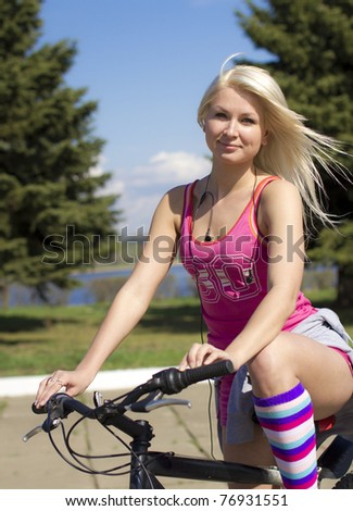 The young beautiful blonde sits on a bicycle