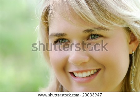 The young beautiful fair-haired woman smiles against a green field.
