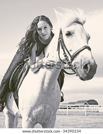 The young beautiful girl embraces a horse - stock photo