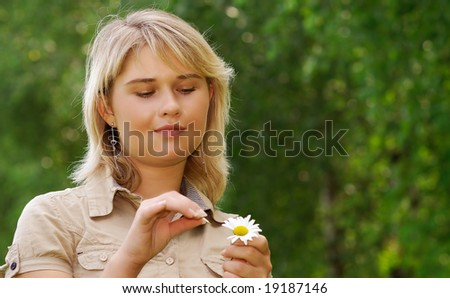 The young beautiful girl guesses about the beloved, tearing off from a camomile petals.