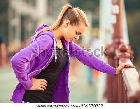 The young beautiful girl with headphones running and doing fitness in city - stock photo