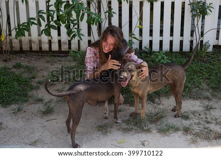 the young beautiful girl with long hair plays with dogs, develops the fashion dressing the stylish woman in her red lips - stock photo