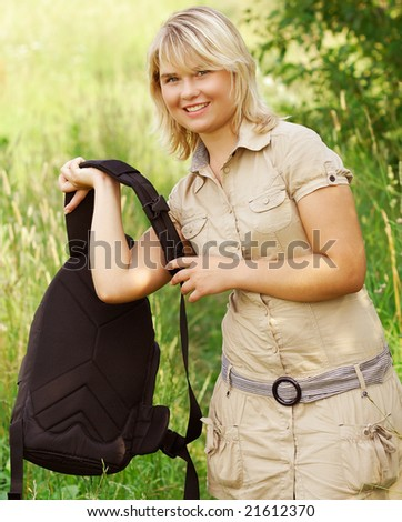 The young beautiful woman dresses the backpack on a shoulder again to go to a way.